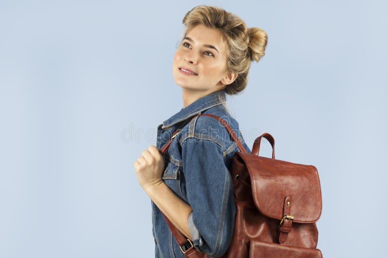 Piękna studencka dziewczyna w drelichowej kurtce z plecakiem na ona ramiona w studiu na błękitnym tle Pojęcie zdjęcie royalty free