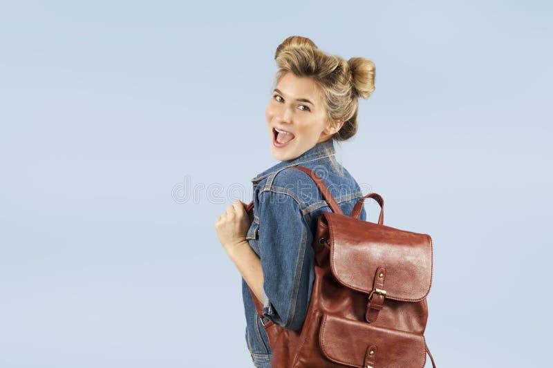 Piękna studencka dziewczyna w drelichowej kurtce z plecakiem na ona ramiona w studiu na błękitnym tle Pojęcie zdjęcia stock