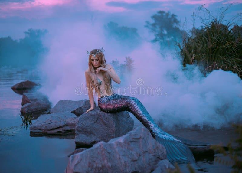 Piękna syrenka siedzi na skale w purpurowej mgle obrazy royalty free