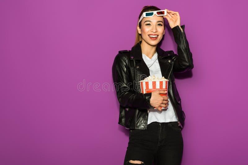 piękna szczęśliwa azjatykcia dziewczyna trzyma popkorn i ono uśmiecha się przy kamerą w 3d szkłach obraz stock