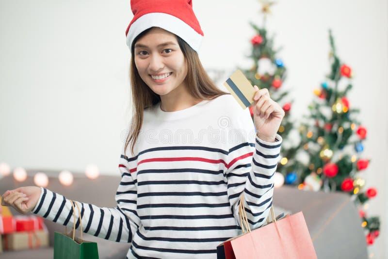 Piękna szczęśliwa azjatykcia dziewczyna z kredytową kartą w jej ręce, Christma obraz stock