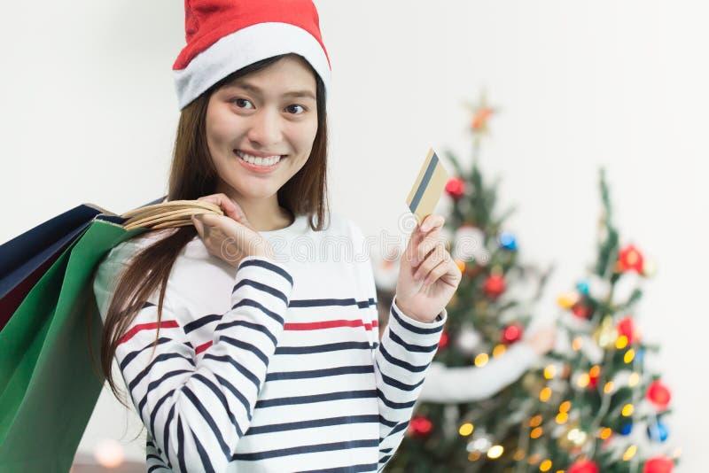 Piękna szczęśliwa azjatykcia dziewczyna z kredytową kartą w jej ręce, Christma zdjęcia stock