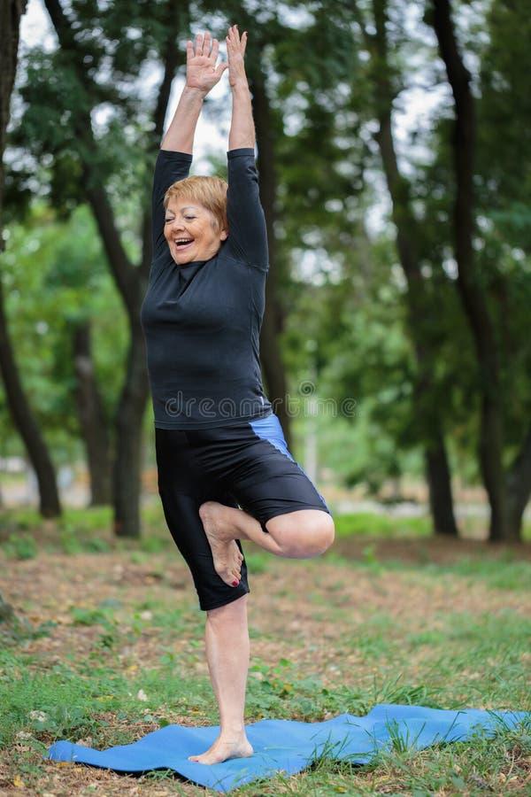 Piękna, szczęśliwa dojrzała kobieta robi joga na parkowym tle, pojęcia gym styl życia ludzie sportów obraz stock