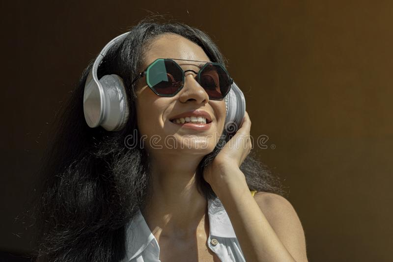 Piękna szczęśliwa dziewczyna w bezprzewodowych hełmofonach cieszy się muzykę zdjęcia royalty free