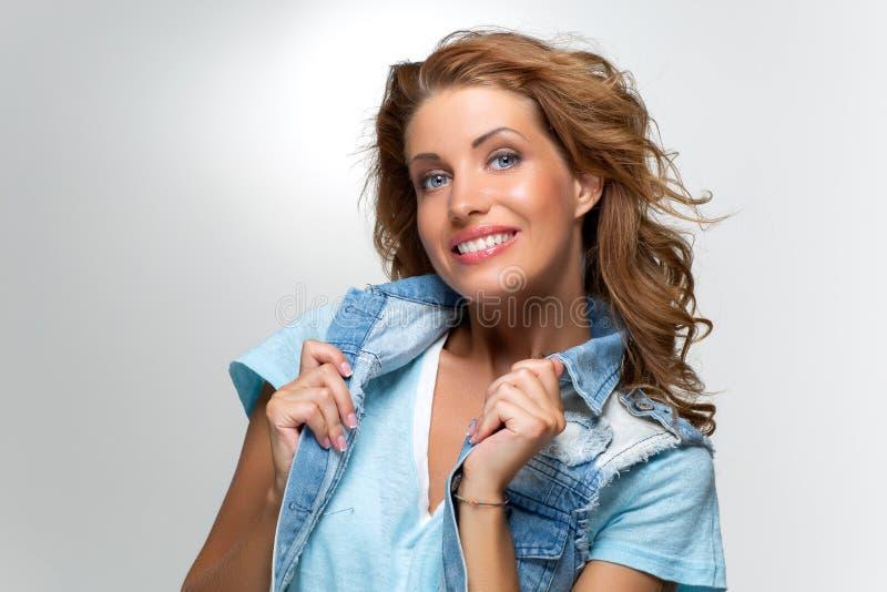 Piękna szczęśliwa dziewczyna w niebiescy dżinsy kurtce zdjęcie royalty free