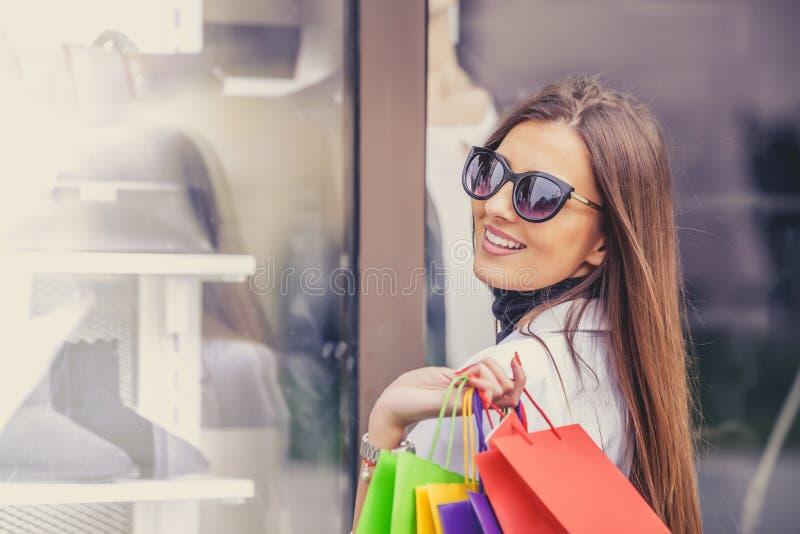 Piękna szczęśliwa dziewczyna w słońc szkłach trzyma torba na zakupy zdjęcia stock