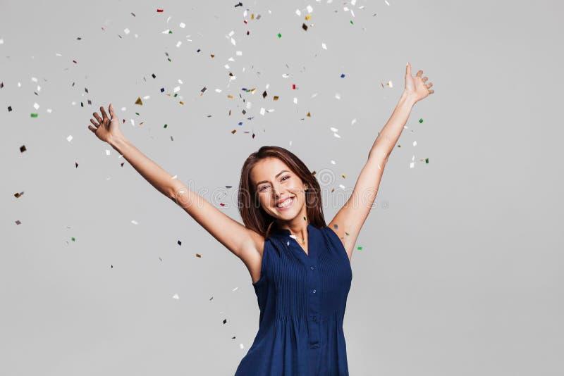 Piękna szczęśliwa kobieta przy świętowania przyjęciem z confetti spada wszędzie na ona Urodziny lub nowego roku wigilii odświętno zdjęcia stock