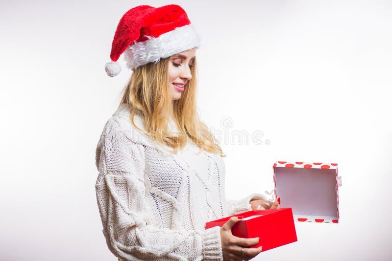 Piękna szczęśliwa kobieta w czerwonym Santa kapeluszu i beżu pulowerze otwiera jej Bożenarodzeniowego prezent, pudełko z faborkie fotografia royalty free