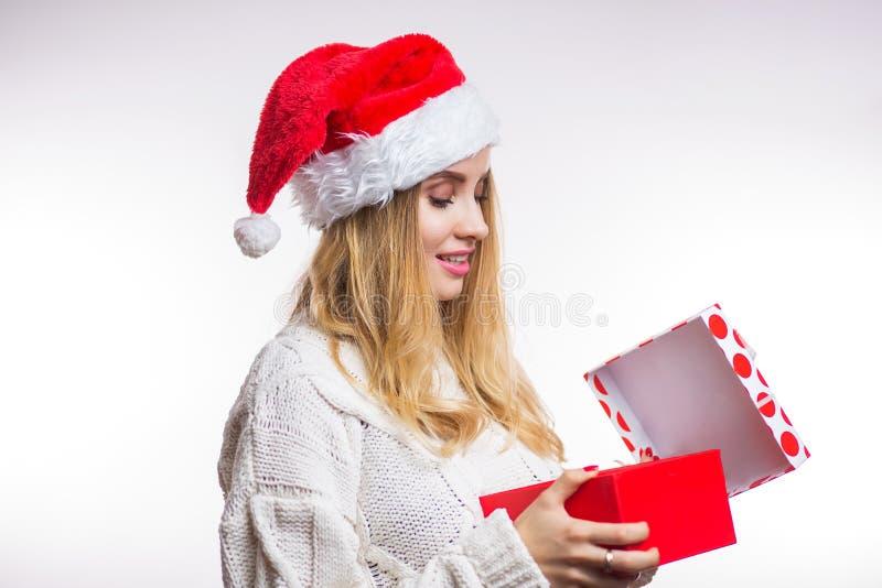 Piękna szczęśliwa kobieta w czerwonym Santa kapeluszu i beżu pulowerze otwiera jej Bożenarodzeniowego prezent, pudełko z faborkie zdjęcia royalty free