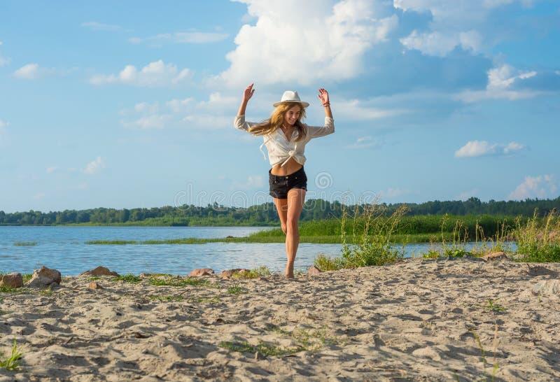 Piękna szczęśliwa młoda kobieta biega along w kapeluszu w skrótach i zdjęcie stock