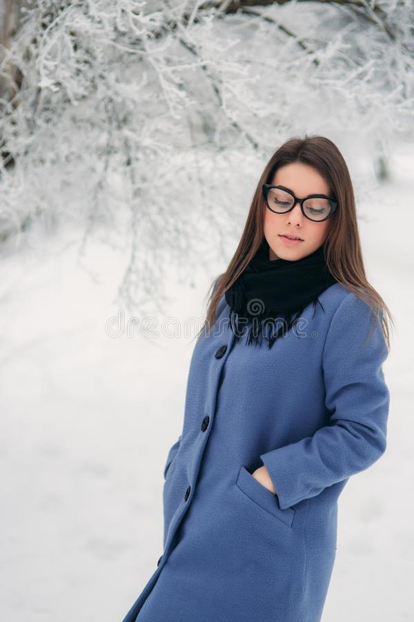 Piękna szczęśliwa młoda kobieta jest ubranym zima żakiet z czarnymi szkłami barwi Błękitnego kobalt i czarnego szalika zakrywając zdjęcie royalty free