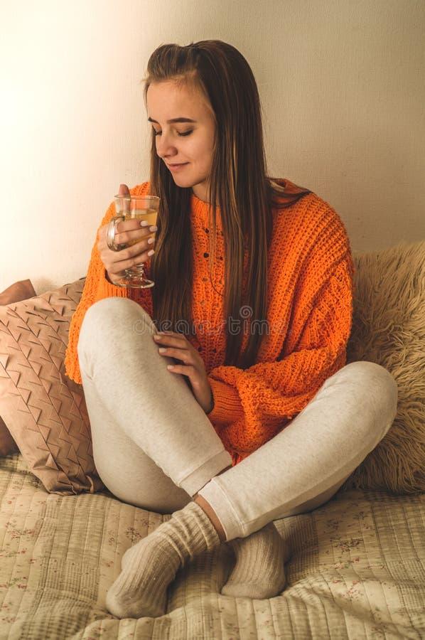 Piękna Szczęśliwa młoda kobieta Pije filiżanka kawy Lub herbaty W łóżku w jaskrawym pomarańczowym pulowerze Uśmiechnięta dziewczy fotografia stock