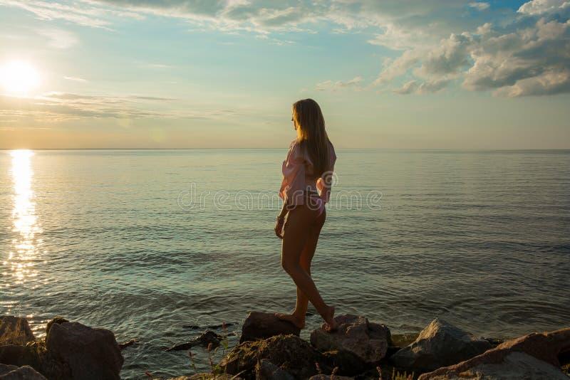 Piękna szczęśliwa młoda kobieta stoi plecy w różowym swimsuit i zdjęcie royalty free