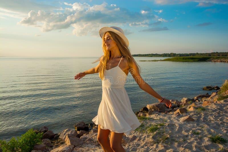 Piękna szczęśliwa młoda kobieta w białej lato atłasu sukni kłębi a obraz royalty free