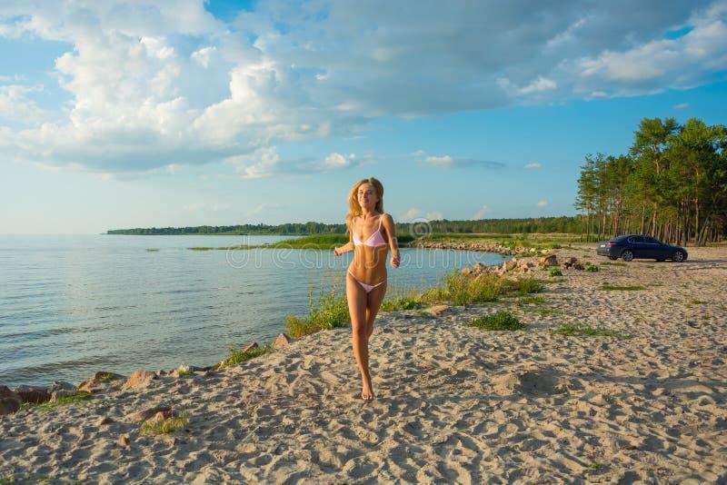 Piękna szczęśliwa młoda kobieta w różowym swimsuit bieg wzdłuż zdjęcia stock