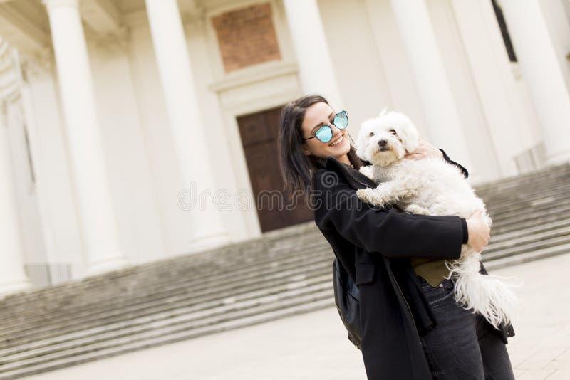 Piękna szczęśliwa młoda kobieta z ślicznym małym psim szczeniakiem fotografia royalty free