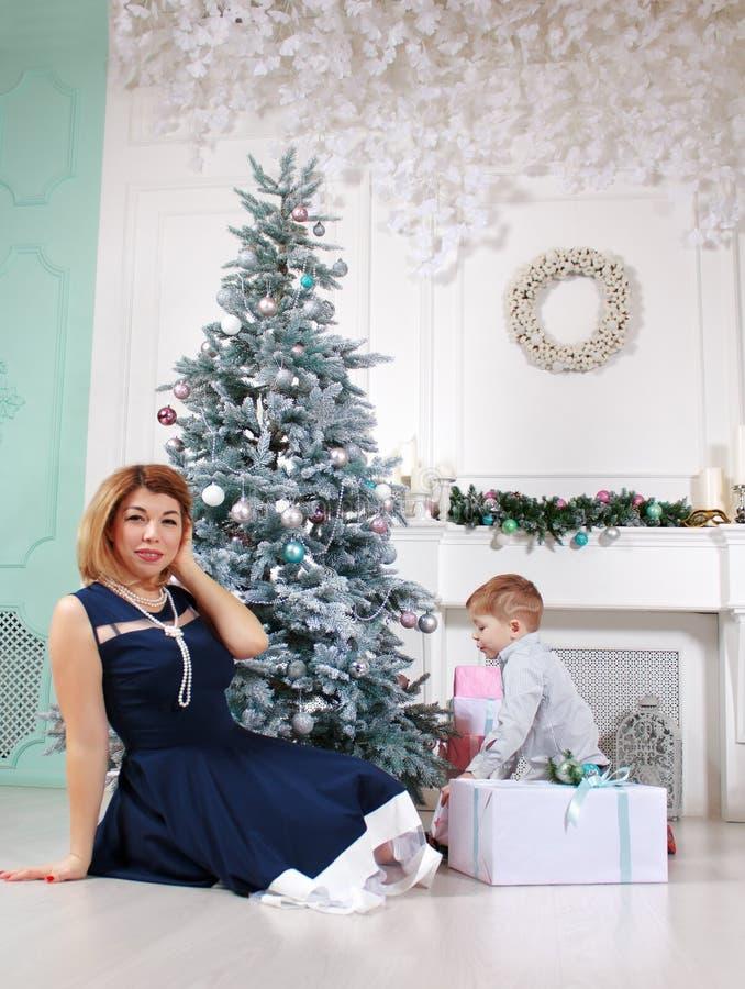 Piękna szczęśliwa matka z jej synem z prezentami blisko dekorującej choinki obraz stock