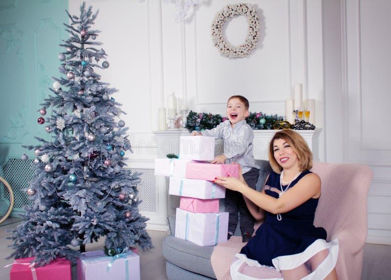 Piękna szczęśliwa matka z roześmianym synem z prezentami na Xmas wigilii fotografia royalty free