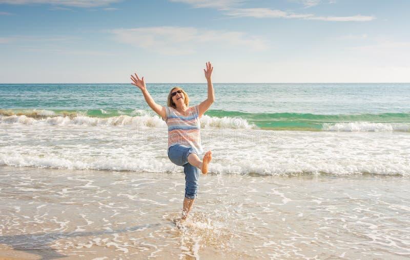 Piękna szczęśliwa starsza kobieta żyje aktywnego emerytury styl życia z radością przy plażą zdjęcie stock