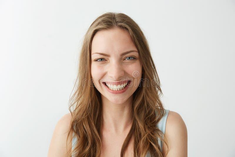 Piękna szczera szczęśliwa dziewczyna uśmiecha się śmiać się patrzejący kamerę nad białym tłem obrazy stock
