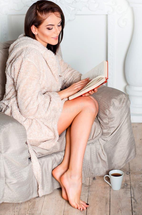 Piękna szczupła dziewczyna w domowym beżowym bathrobe obsiadaniu w beig obraz royalty free