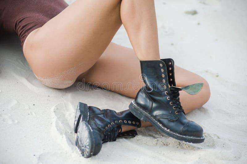 Piękna, szczupła kobieta, iść na piechotę w wysokich rzemiennych butach Dziewczyna z gęstymi butami na piasku zdjęcia stock