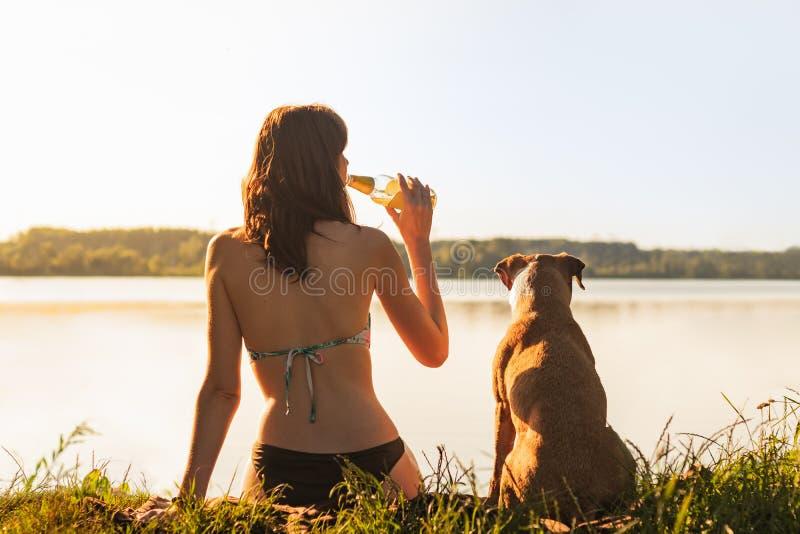 Piękna szczupła kobieta z zwierzę domowe psem cieszy się piękny celowniczy pobliskiego zdjęcie stock