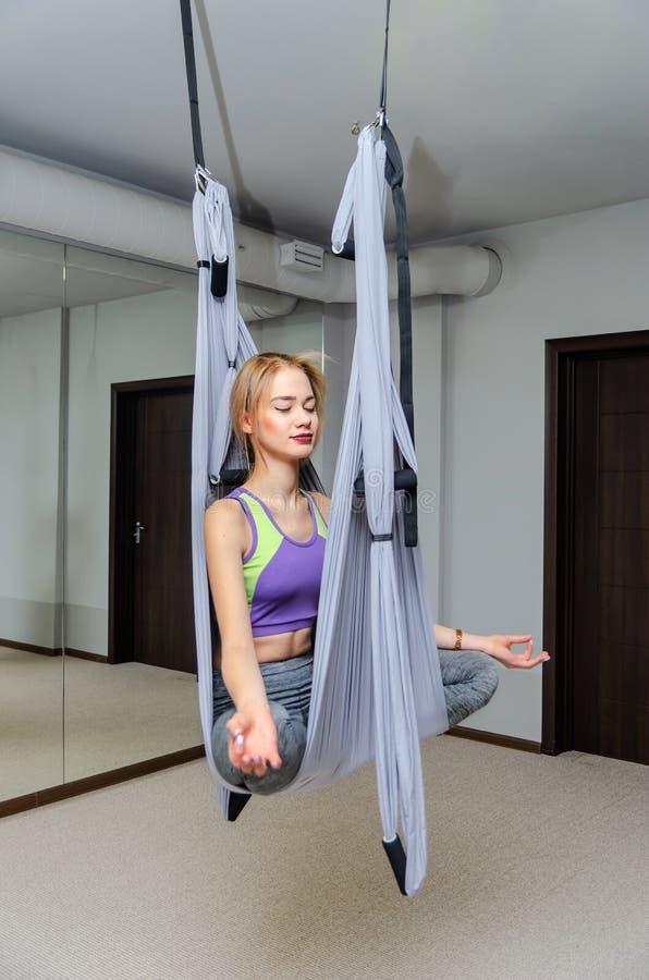 Piękna szczupła sportowa blondynki kobieta robi komarnicy joga w hamaku w studiu obrazy royalty free