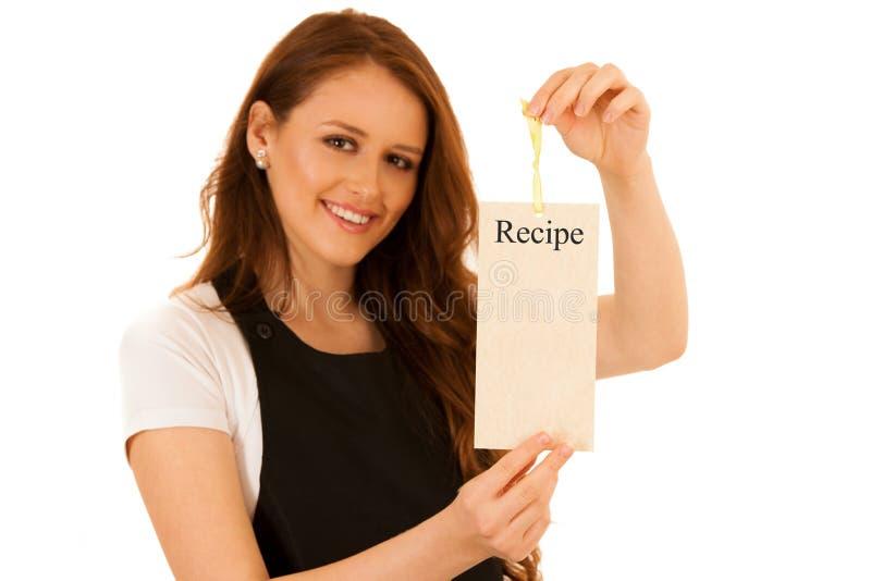 Piękna szef kuchni kobieta trzyma kartę z przepisem odizolowywającym nad wh fotografia royalty free