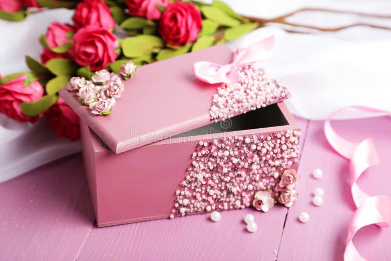 Piękna szkatuła z kwiatami na purpurowym drewnianym tle obraz stock