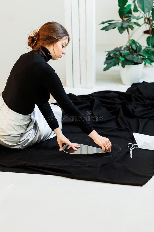Piękna szwaczka, ciie czarną tkaninę na pracownianej podłodze zdjęcia stock