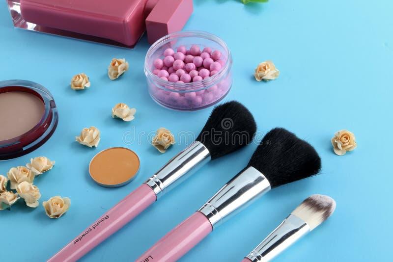 Piękna tło z twarzowymi kosmetycznymi produktami, liśćmi i czereśniowym okwitnięciem na pastelowym błękitnym desktop tle, Nowożyt zdjęcia royalty free