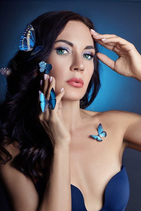 Piękna tajemnicza kobieta z motyla błękitnym kolorem na twarzy, brunetce i papierowych sztucznych błękitnych motylach na dziewczy obraz royalty free