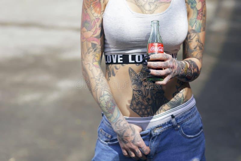 Piękna tatuująca kobieta trzyma butelkę koka-kola oryginał obraz royalty free