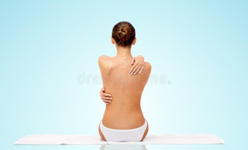 Piękna toples młoda kobieta na ręczniku od plecy obrazy stock