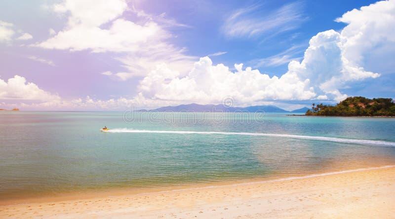 Piękna tropikalna peleryna Fale oceaniczne i mętne niebo Krystalicznie niebieskie morze, wyspa, rower wodny Wody oceaniczne, obraz royalty free