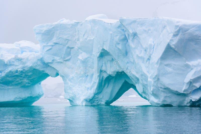 Piękna turkusowego błękita góra lodowa unosi się w Antarktycznym, przeciw mgłowemu tłu zdjęcie stock