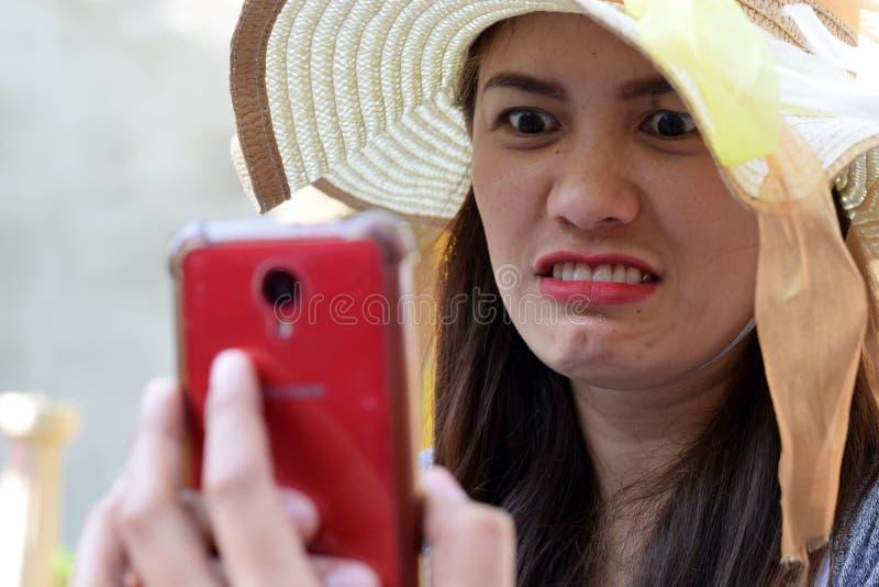 Piękna twarz jest ubranym Niedziela kapelusz wiek średni kobieta dokuczał gniewną twarz wyszukuje internet w mądrze telefonie obrazy stock