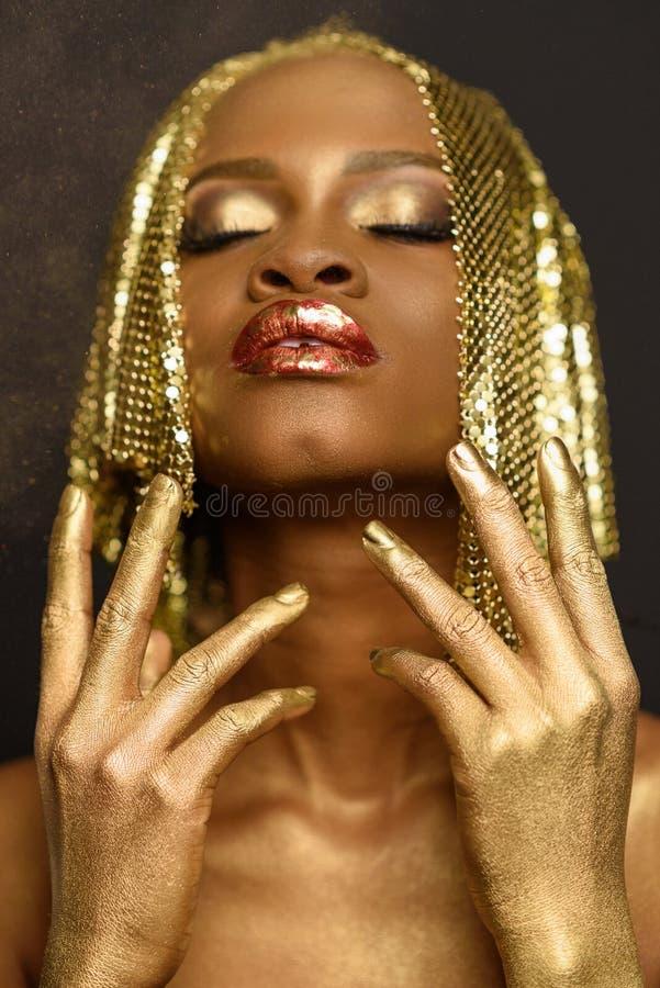 Piękna twarz młoda afroamerykańska kobieta z złocistym makijażem, perfect skórą i zamykającymi oczami odizolowywającym na czarnym fotografia royalty free