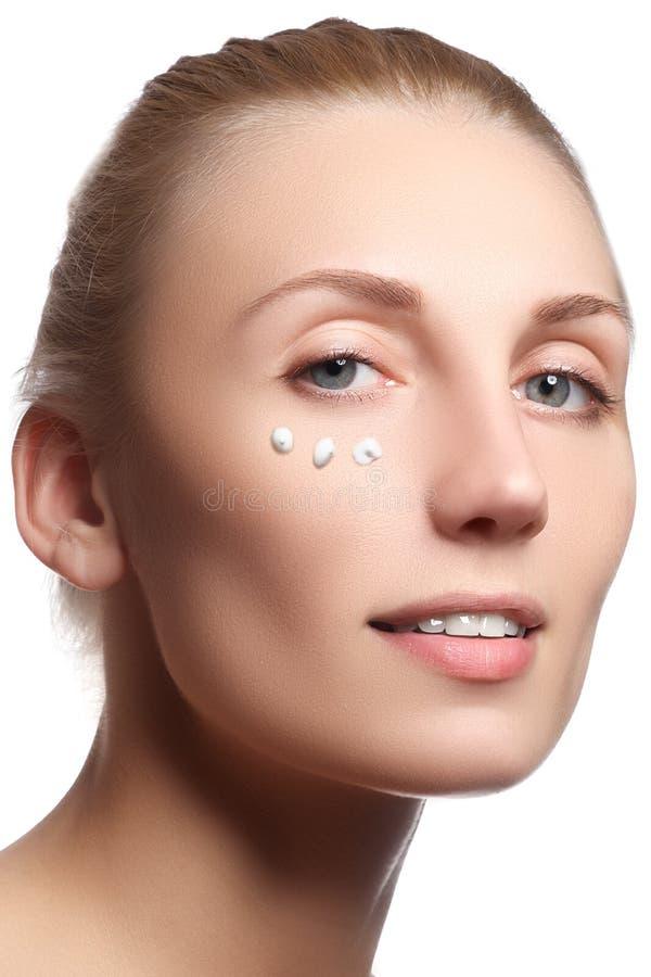 Piękna twarz młoda kobieta z kosmetyczną śmietanką na policzku Skóry opieki pojęcie Zbliżenie portret odizolowywający na bielu Za obrazy stock