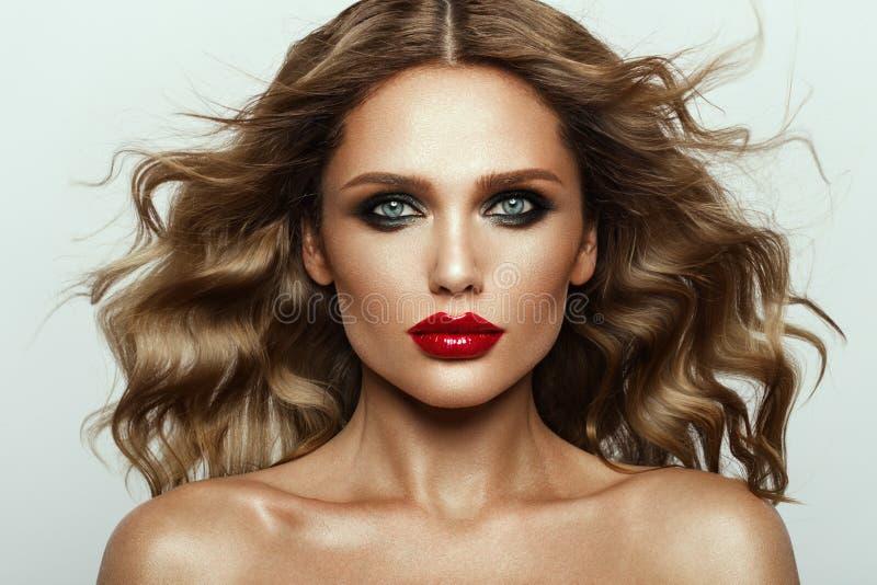 Piękna twarz moda model z niebieskimi oczami kręcone włosy czerwone usta fotografia royalty free
