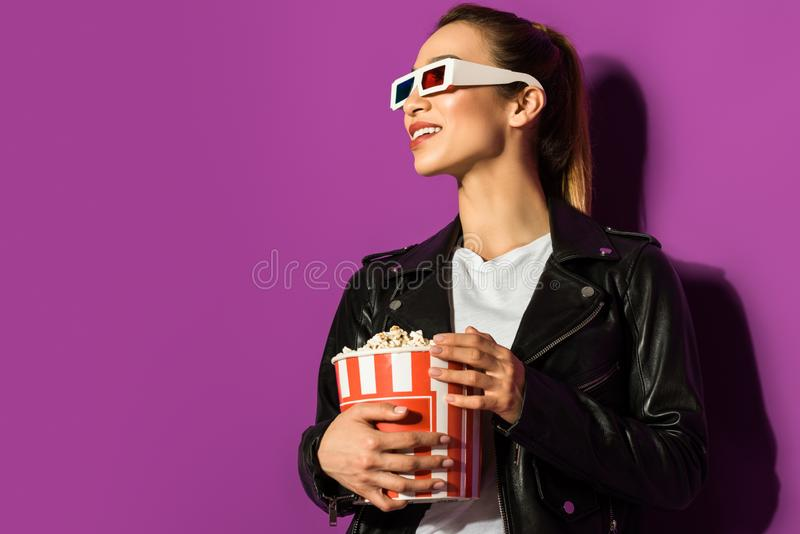 piękna uśmiechnięta azjatykcia dziewczyna trzyma popkorn i patrzeje daleko od w 3d szkłach fotografia royalty free