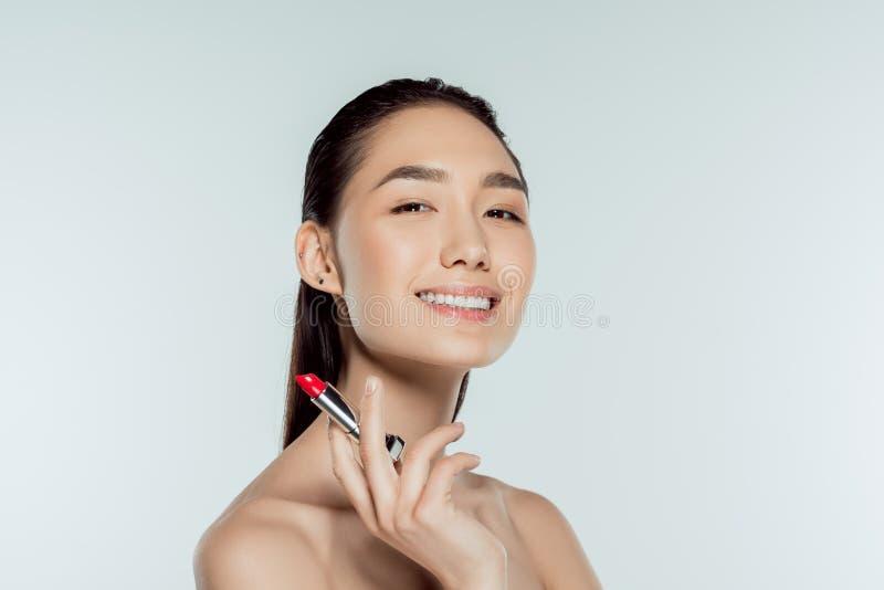 piękna uśmiechnięta azjatykcia kobiety mienia czerwieni pomadka obraz royalty free