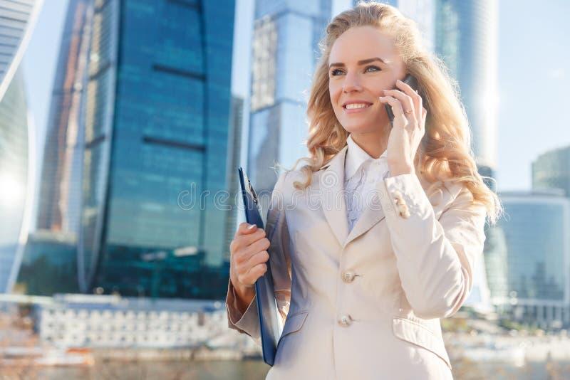 Piękna uśmiechnięta biznesowa kobieta opowiada na telefonie komórkowym outdoors obrazy stock