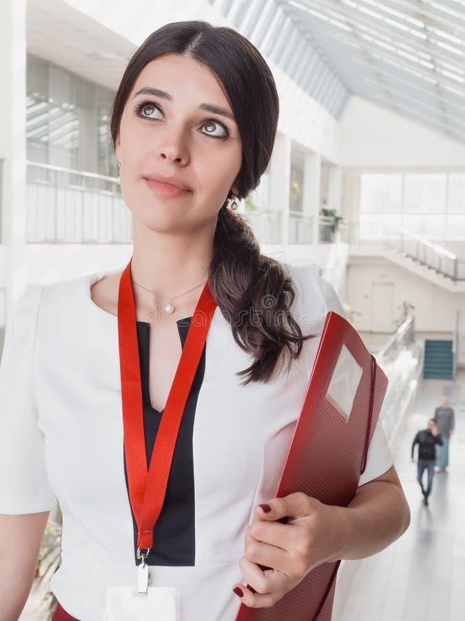 Piękna Uśmiechnięta bizneswoman pozycja Przeciw Białemu biura tłu Portret Biznesowa kobieta Z falcówką w Ona ręki obrazy royalty free