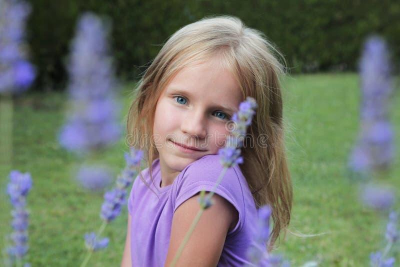 Piękna uśmiechnięta blond błękitnooka dziewczyna, portret w lawendowi kwiaty obrazy stock