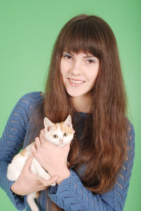 Piękna uśmiechnięta brunetki dziewczyna i jej kot obrazy royalty free
