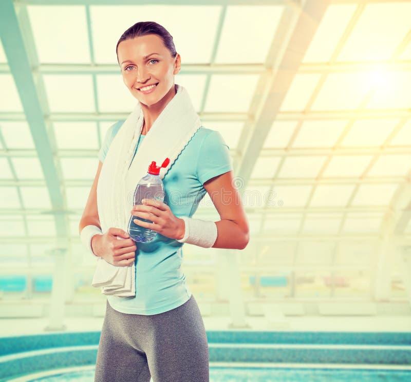 Piękna uśmiechnięta caucasian kobieta jest ubranym sporta odzieżowego holdin fotografia stock