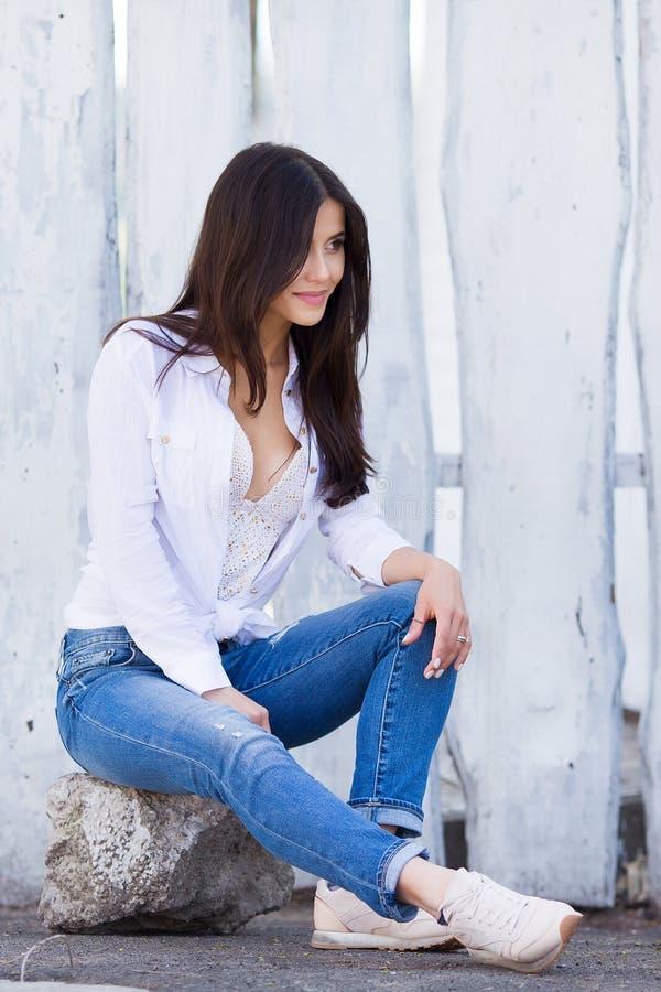Piękna uśmiechnięta dziewczyna jest ubranym pustą białą koszula i cajgi pozuje przeciw ulicznej drewnianej ścianie Minimalistyczn obraz stock
