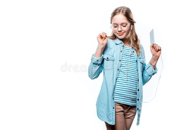 Piękna uśmiechnięta dziewczyna słucha muzykę z smartphone w słuchawkach obrazy stock